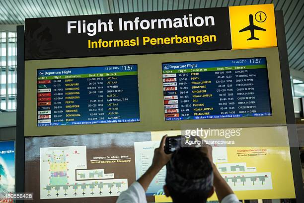 A tourist guide captures the flight informationn at Ngurah Rai International airport on July 13 2015 in Denpasar Bali Indonesia Bali's international...