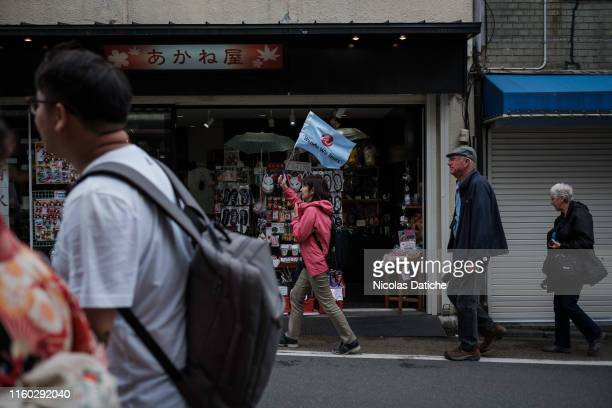 A tourist guide holding a small flag walks in a street of Kyoto followed by tourists With the increase of inboud tourism in Japan supporting by the...