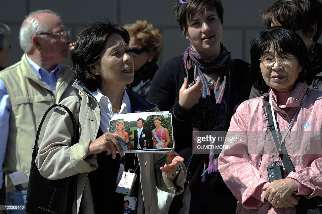 A tourist guide holds a picture of the c