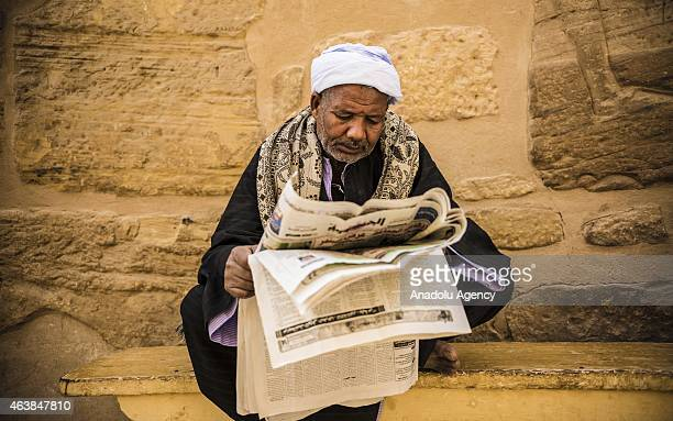 A tourist guide reads newspaper at Ramesses III Mortuary Temple also known as Medinet Habu Complex in west of Luxor Egypt on February 19 2015 The...