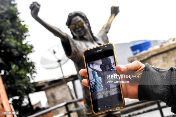 A tourist guide shows a mobile phone with the picture of US pop icon Michael Jackson´s statue with an assault rifle hanging around its neck at Santa...