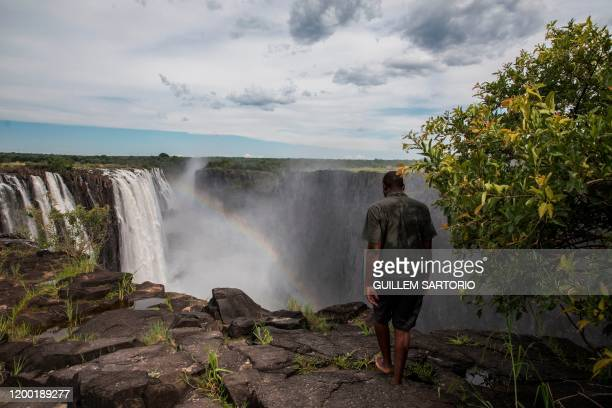 A tourist guide walks near the edge of the Victoria Falls in Livingstone on January 23 2020 The Victoria Falls a UNESCO world heritage site measuring...