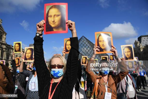 Tourist Guides hold reproductions of the Mona Lisa outside the Louvre museum as it reopens its doors following its 16 week closure due to lockdown...