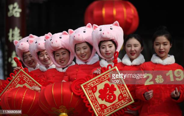 Tourist guides wearing pig hats hold Chinese knots and red lanterns to send New Year greetings to tourists at Yangzhou Slender West Lake scenic area...