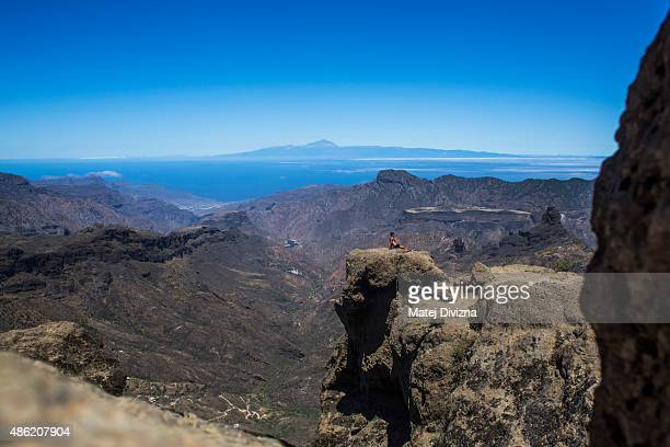 A tourist has a rest near Roque Nublo a volcanic rock with Pico del Teide on Tenerife island and Roque Bentayga in the background on July 26 2015...