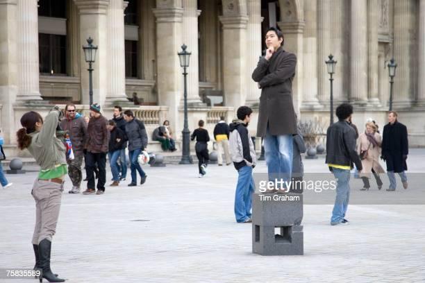 Tourist has his photograph taken balancing on posing plinth outside the Louvre Museum Paris France