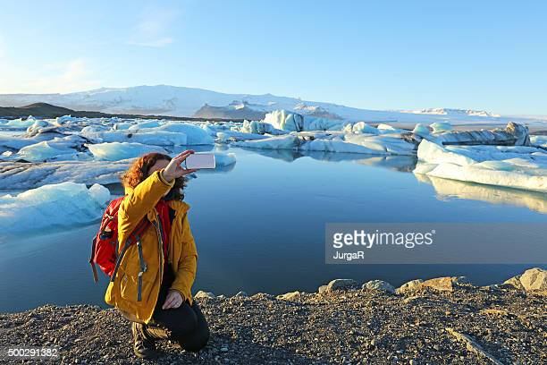 tourist hiker taking selfie at jokulsarlon glacial lagoon in iceland - glacier lagoon stock photos and pictures