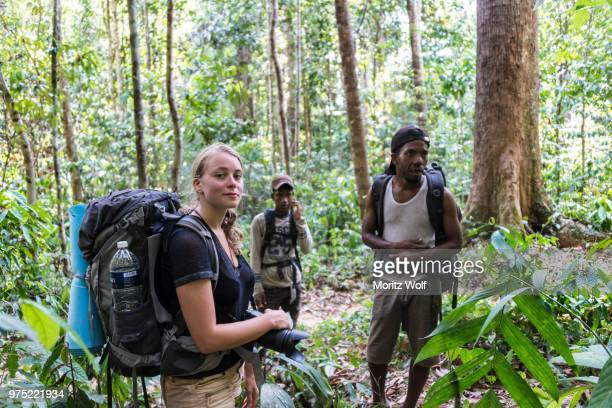 tourist, hiker, young woman with a backpack in the jungle with two orang asil men, taman negara, malaysia - taman negara national park stock photos and pictures