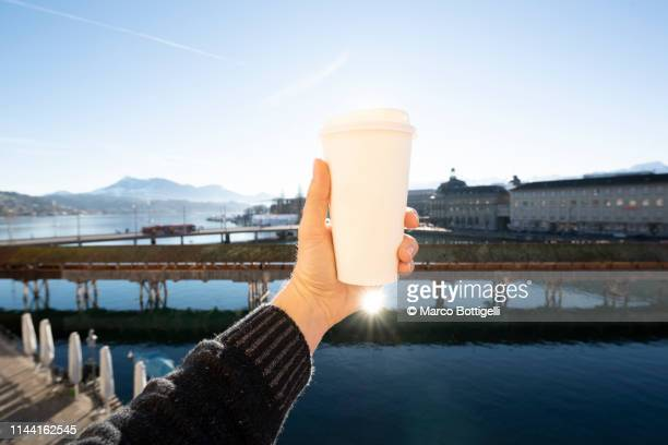 tourist holding a coffee paper cup in lucerne, switzerland - 使い捨て製品 ストックフォトと画像