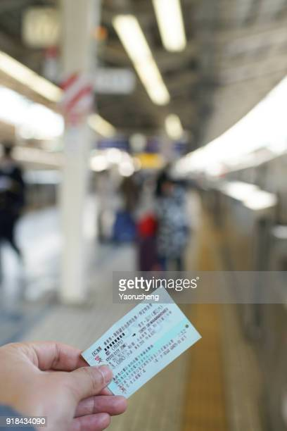 tourist holding a Shinkansen Train ticket  from Kyoto to Tokyo at Tokyo station platform,Japan.