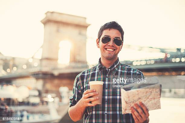 Tourist holding cup of coffee and map