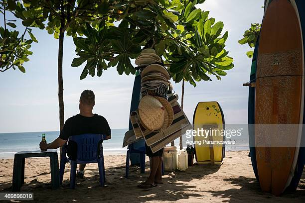 A tourist holds a bottle of beer at Kuta Beach on April 16 2015 in Kuta Bali Indonesia Indonesia on April 16 banned small retailers from selling beer...