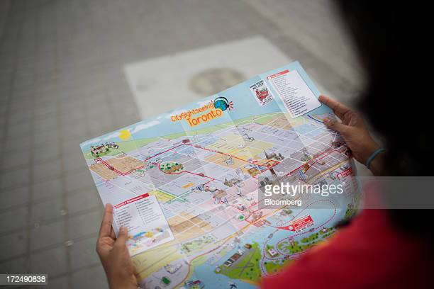 A tourist holds a sightseeing map in Toronto Ontario Canada on Monday July 1 2013 Total arrivals from Canadian Tourism Commissions international...