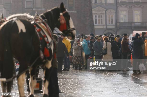 A tourist horse carriage passes next to the 21st Edition of the Biggest Christmas table in Europe at the Main Square in Krakow The so called...