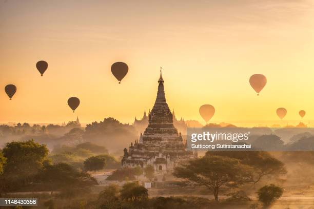 tourist hot air balloon over ancient pagoda at bagan in myanmar, tourists watching sunrise over ancient city - tempel stockfoto's en -beelden