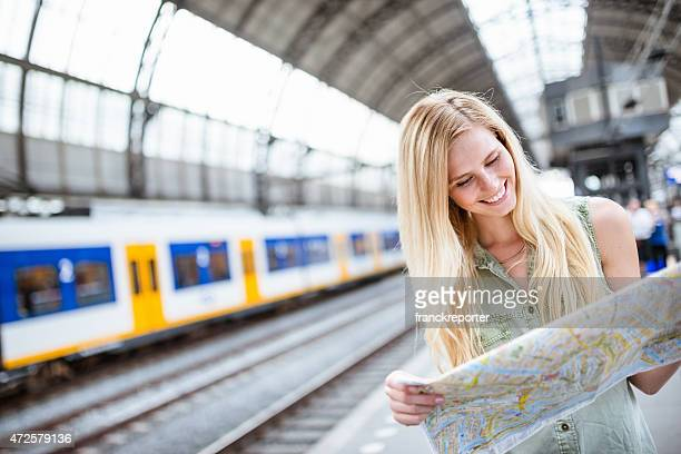 tourist in amsterdam looking map of the city