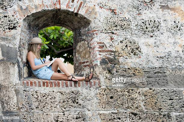 Tourist in Cartagena reading a book in the wall