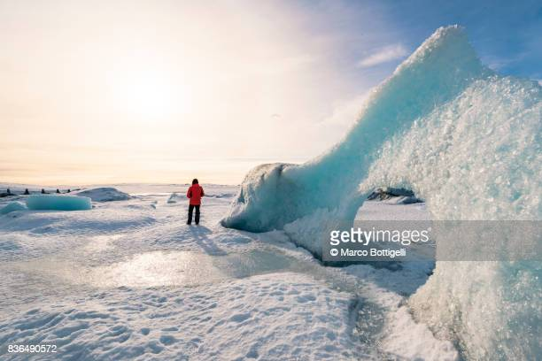 tourist in fjallsarlon glacier lagoon. iceland. - red coat stock pictures, royalty-free photos & images