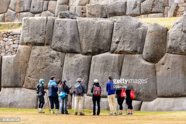 Tourist in front of huge stone wall at Saqsaywaman, Peru