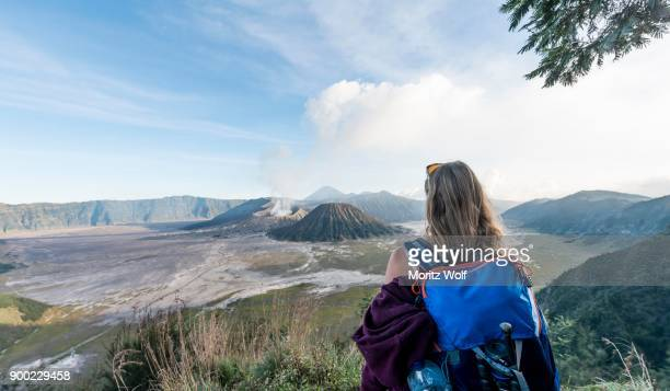 tourist in front of landscape, smoking volcano mount bromo, mt. batok at front, mt. kursi at back, mt. gunung semeru, bromo tengger semeru national park, java, indonesia - mt bromo stock photos and pictures