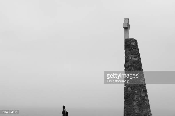 A tourist in front of stone monument at Cabo da Roca, Portugal