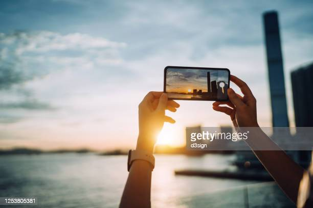 tourist in hong kong taking photos of iconic city skyline and beautiful sunset with smartphone by the promenade of victoria harbour - fotohandy stock-fotos und bilder