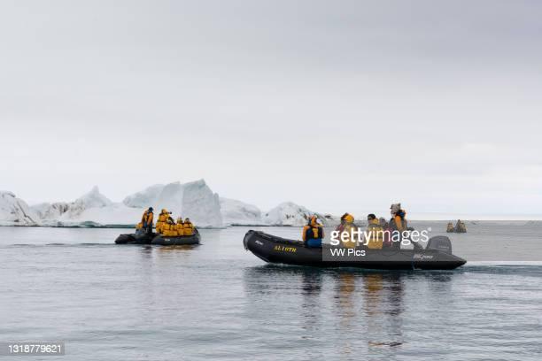 Tourist in inflatable boats, Vibebukta, Austfonna, Nordaustlandet, Svalbard Islands, Norway..