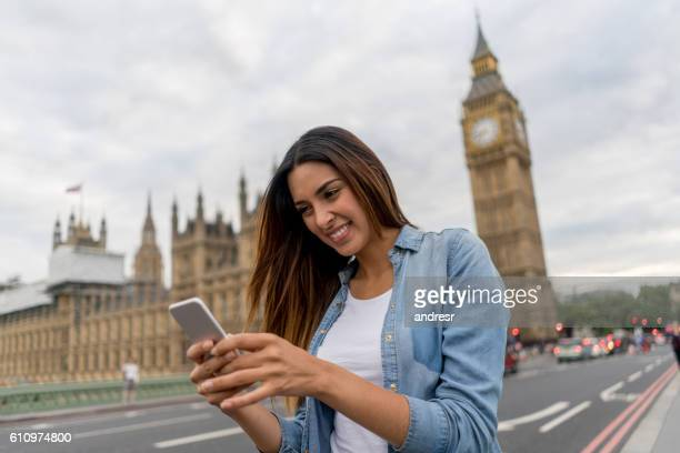 Tourist in London using app on her mobile phone