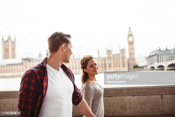 tourist in london walking together - monument station london stock photos and pictures