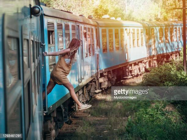 tourist in sri lanka riding train, hanging outside - sri lanka stock pictures, royalty-free photos & images