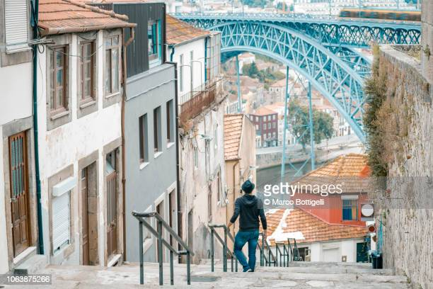 tourist in the old town of porto looking at dom luis i bridge - porto portugal stock pictures, royalty-free photos & images