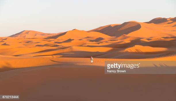 Tourist in The Sahara Desert at Sunset in Morocco Africa.