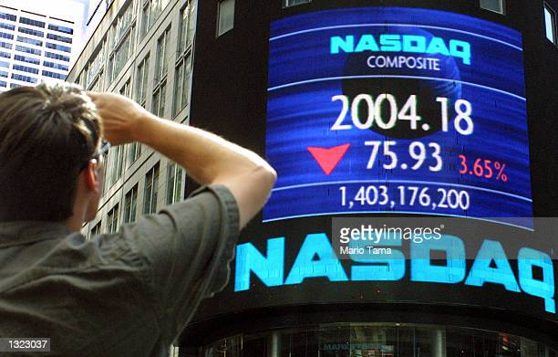 A tourist in Times Square views a Nasdaq ticker July 6 2001 in New York City The major US stock indexes tumbled to 10week lows with the the Nasdaq...