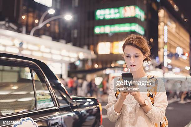 Tourist in Tokyo texting at the street by night