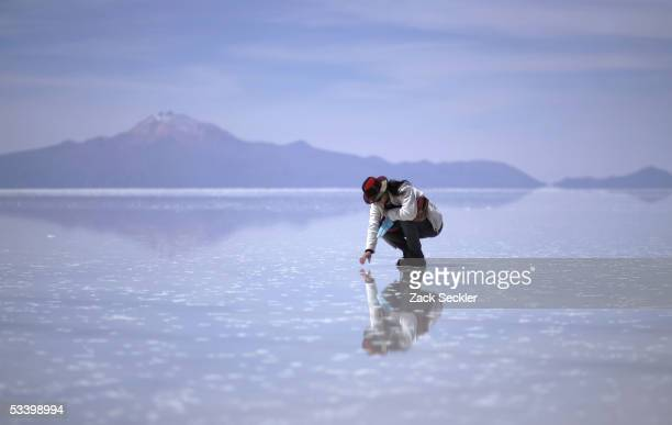 A tourist inspects a salt bed in the Salar de Uyuni January 24 2005 in Bolivia Bolivia's Salar de Uyuni the world's largest salt flat at 4680 square...
