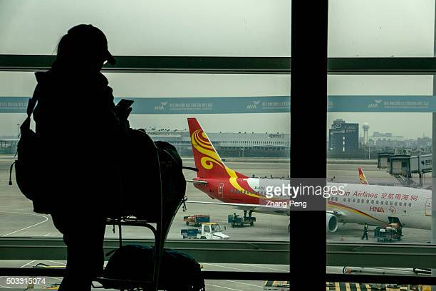 A tourist is waiting for boarding after the plane finishes ground service The year of 2015 is the most profitable year for Chinas aviation industry...