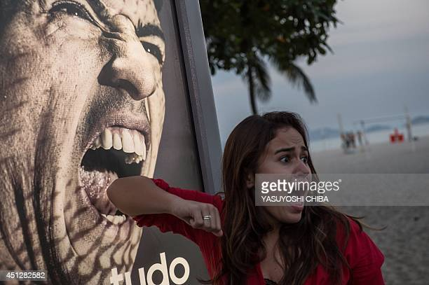 Tourist jokes in front of an advertisement with the portrait of Uruguay's forward Luis Suarez at Copacabana beach in Rio de Janeiro, Brazil, on June...
