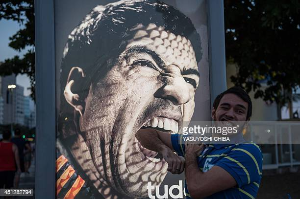 A tourist jokes in front of an advertisement with the portrait of Uruguay's forward Luis Suarez at Copacabana beach in Rio de Janeiro Brazil on June...