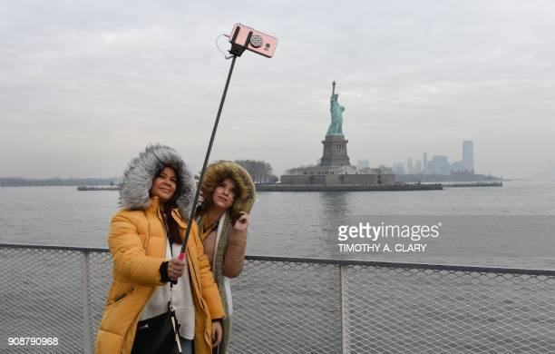 TOPSHOT Tourist Jorden Lyle and Tory Plunkett from England take pictures aboard the Miss Ellis Island Ferry Boat as the first visitors arrive Monday...