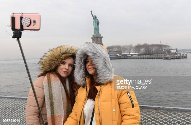 Tourist Jorden Lyle and Tory Plunkett from England take pictures aboard the Miss Ellis Island Ferry Boat as the first visitors arrive Monday morning...