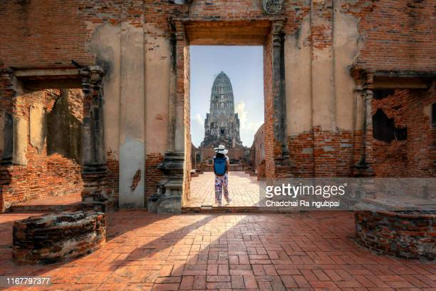 tourist journey asia thailand temple concept. women tourists and backpacks are walking. see wat ratchaburana in ayutthaya, thailand. ancient ruins in ayutthaya province is a world heritage site and is a historical tourist attraction. - ayuthaya province stock pictures, royalty-free photos & images
