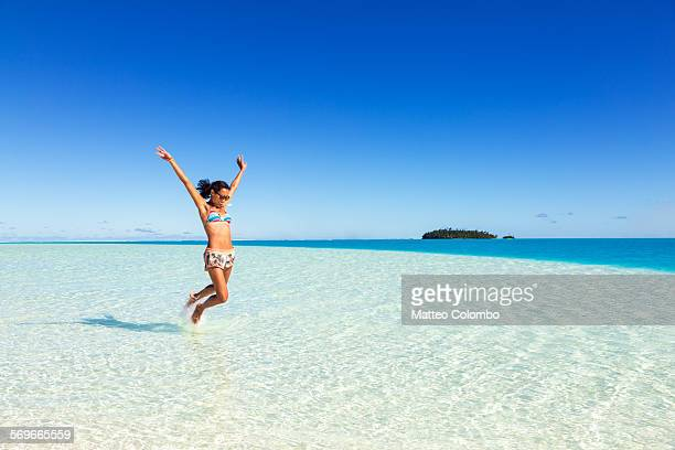 Tourist jumping in the blue lagoon of Aitutaki