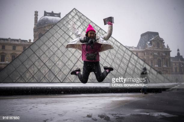 TOPSHOT A tourist jumps in front of the Louvre Pyramid in Paris on February 9 2018 / AFP PHOTO / Lionel BONAVENTURE