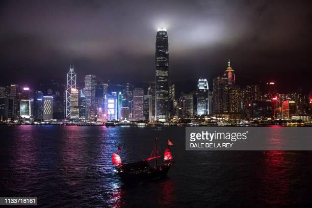 TOPSHOT A tourist junk boat sails in Victoria Harbour before the Earth Hour environmental campaign in Hong Kong on March 30 2019 The 13th edition of...
