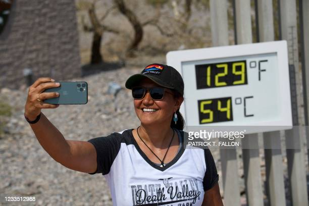 Tourist Karina Simpson takes pictures with a thermometer display showing temperatures of 129 Degrees Fahrenheit at the Furnace Creek Visitor's Center...