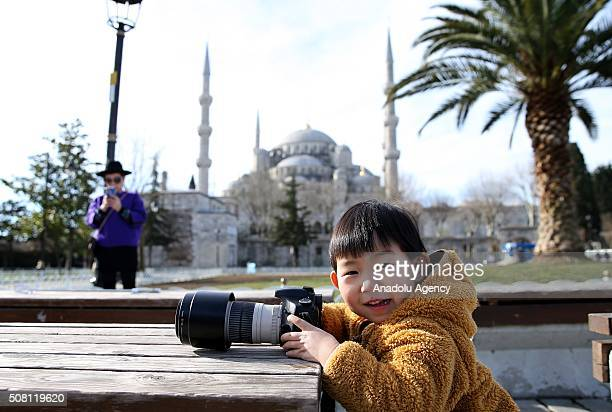 A tourist kid takes a photograph Sultanahmet square in Istanbul Turkey on February 3 2016 Sultanahmet square one of the most attractive destination...
