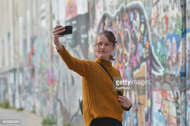 A tourist lady takes a selfie near the political and social mural paintings on Israeli West Bank barrier in Bethlehem Tuesday 13 March 2018 in...