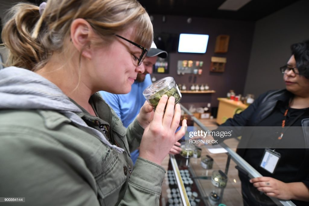 Tourist Laura Torgerson, visiting from Arizona, smells cannabis buds at the Green Pearl Organics dispensary on the first day of legal recreational marijuana sales in California, January, 1, 2018 in Desert Hot Springs, California. / AFP PHOTO / Robyn Beck