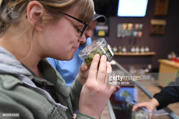 Tourist Laura Torgerson visiting from Arizona smells cannabis buds at the Green Pearl Organics dispensary on the first day of legal recreational...