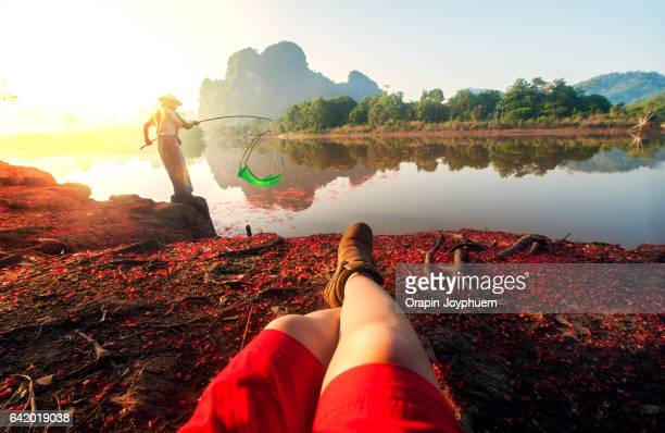 A tourist lay down on the river bank to watch people fishing.